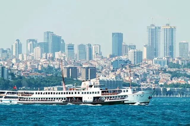 Fähre vor der Innenstadt von Istanbul am Bosporus. Im Hintergrund sind einige Hochäuser zu sehen.