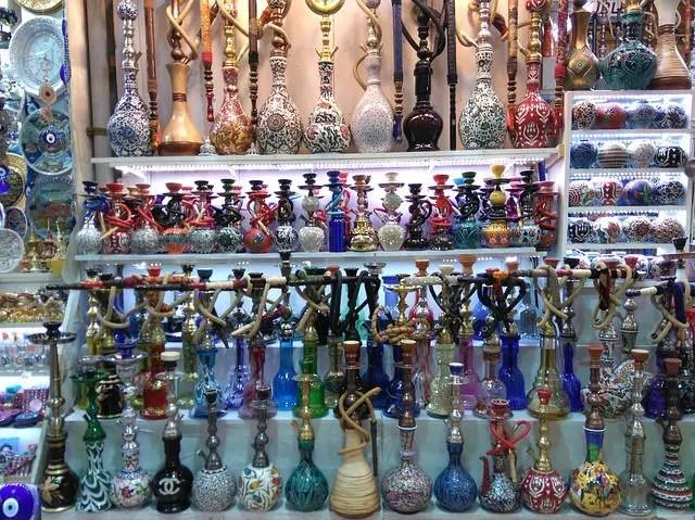Nargile aus Glas und Porzellangefäßgen für das Wasser in verschiedenen bunten Farben im Regal eines Standes an einem Bazar in der Türkei