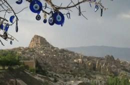 An einem Baum hängen türkische Augen (Nazar Amulett - klein augenförmig geformte Anhänger in blauer, weißer und schwarzer Farbe) an einem Baum. Im Hintergrund ist die sandfarbene Landschaft von Kappadokien mit ein paar grünen Bäumen vor der Festung Uchisar zu sehen.