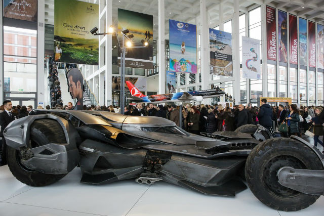 Bamobil am Eingang der Internationalen Tourismusmesse in Berlin. Dahinter hängt ein Modellflugzeug von Turkish Airlines und Pappfiguren von Batman und Superman mit dem Hinwweis, dass Turkish Airlines der offizielle Airline Partner des Films ist.