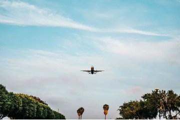 Foto eines startenden Flugzeuges. Aufgenommen vor der Starbahn. Es ist die Unterseite des Flugzeuges zu sehen. Am unteren Teil des Fotos sind Reihen von Bäumen links und rechts zu sehen die genau parallel zur Startbahn stehen.