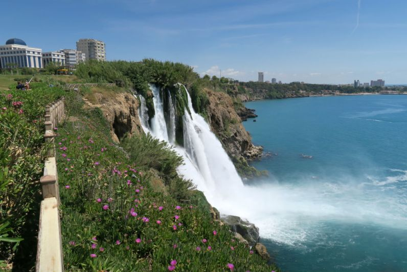Auf der oberen Seite der Klippen sind ein paar Blumen zu sehen. Das Wasser des Düden Wasserfalls.