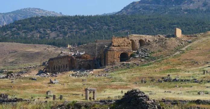 Blick auf das an einem Hügel gebaute Amphietheater. Die Sitzreihen sind noch sehr gut erhalten. Ein Teil der Bühne ist eingestürzt. Davor sind noch andere Ruinen von Bauwerken zu sehen.