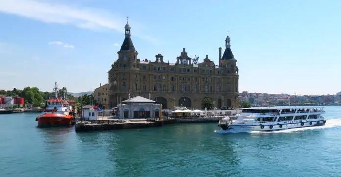 Der am Bosporus stehende Haydarpasa Bahnhof. Aufgenommen von einer Fähre. Am Bosporus ist ein Schiff zu sehen. Vor dem Bahnhof ist ein Restaurant mit Sonnenschirmen.