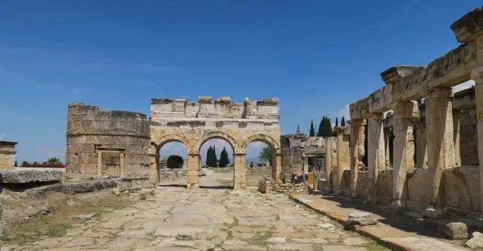 Das aus drei Torbögen bestehende Westtor von Hierapolis. Es ist noch gut erhalten. Auf der linken Seite sind die Reste eines Turms zu sehen. Rechts sind die Ruinen der Latrinen.