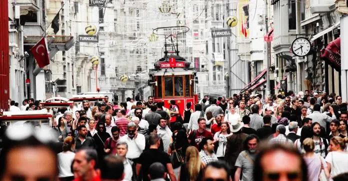 Hunderte Menschen gehen durch die Istiklal Straße. Dazwischen fährt eine alte, rote Straßenbahn durch die Menschenmengen.