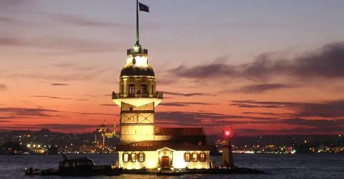 Blick von der asiatischen Seite Istanbuls auf den Lenaderturm. Die Aufnahme ist nach Sonnenuntergang entstanden. Der Himmel ist rötlich gefärbt. Hinter dem ehemaligen Leuchtturm ist der Stadttteil Sultanahmet mit der Hagia Sophia und der Blauen Moschee zu sehen.