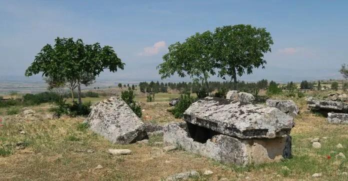 Steinsarkophag mit einem geöffneten Verschluss. Im Hintergrund sind ein paar Bäume zu sehen.