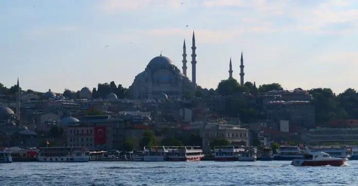 Silhouette der Süleymaniye Moschee bei Sonnenuntergang. Aufgenommen von der Galata Brücke. Davo sind Boote und das Goldene Horn zu sehen.