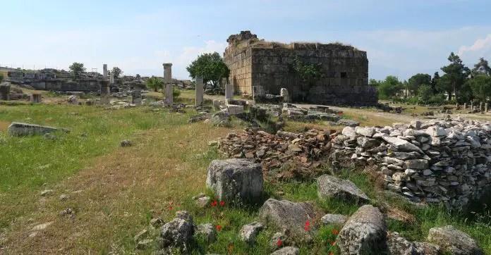 Gut erhaltenen Ruinen des Apollo Tempel. Es sind noch an allen Seiten Mauern zu sehen. Davor stehen einige weiße Marmor Säulen. Im Vordergrund ist eine Wie mit roten Blumen zu sehen.