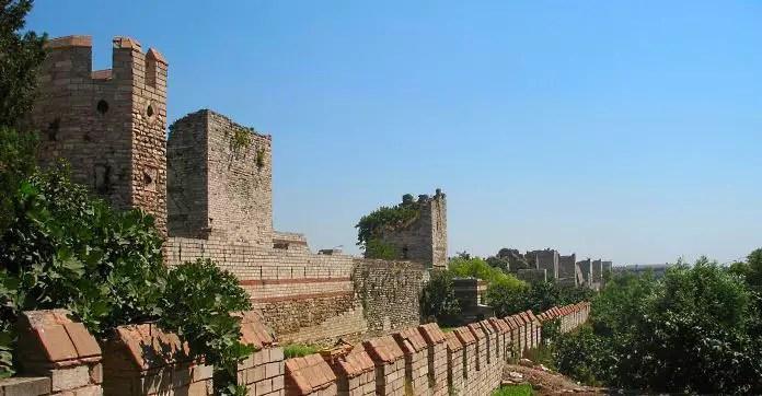 Blick auf die drei hintereinanderliegende Mauern der Theodosianischen Mauer. Links ist die kleinste, niedrigste Mauer zu sehen, dahinter eine höhere und ganz links eine hohe Mauer mit vielen Türmen.