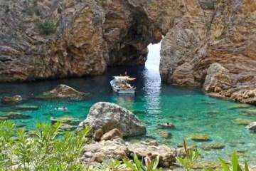 Blick auf ein 10 Meter hohes Felsentor, dass die Piratenbucht an den Ruinen der antiken Stadt Antiochia ad Cragnum mit dem Meer verbindet. Im türkisblauen Wasser ist ein Schiff zu sehen.