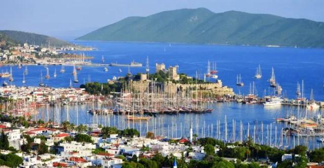 Blick von einem Hügel auf den Hafen und die Burg von Bodrum. Es sind viele Segelschiffe zu sehen. Dahinter sind Inseln zu sehen.
