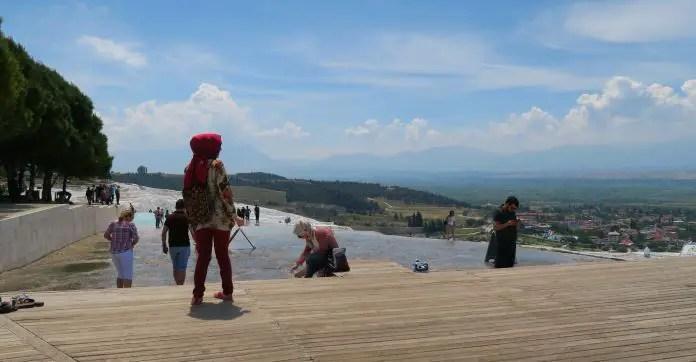 Holzsteg oberhalb der Kalkterrassen. Eine Frau mit Kopftuch zieht sich gerade ihre Schuhe aus. Eine andere Schaut gerade in die Ferne und auf das darunterliegende Tal hinunter.