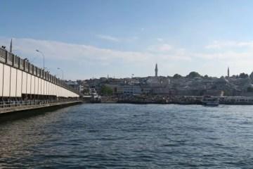 Die Norseite der Galatabrücke mit den Sonnensegeln auf der unteren Seite der Brücke. Dahinter liegen die Restaurants. Auf der oberen Brückenseite stehen Fischer. Auf der rechten Seite des Bildes ist die Süleymaniye Moschee zu sehen.
