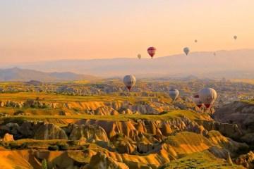 Dutzende Heißluftballone schweben über der zerklüfteten Landschaft Kappadokiens.