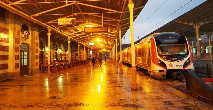 Station der Istanbul Verkehrsbetriebe mit einem eingefahrenen weißen Zug und wenigen Menschen auf dem gut beleuchteten Bahnsteig.