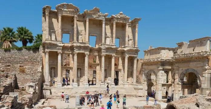 Die Mauer der Celus Bilbiothek in Ephesos mit einigen Touristen die davor stehen.