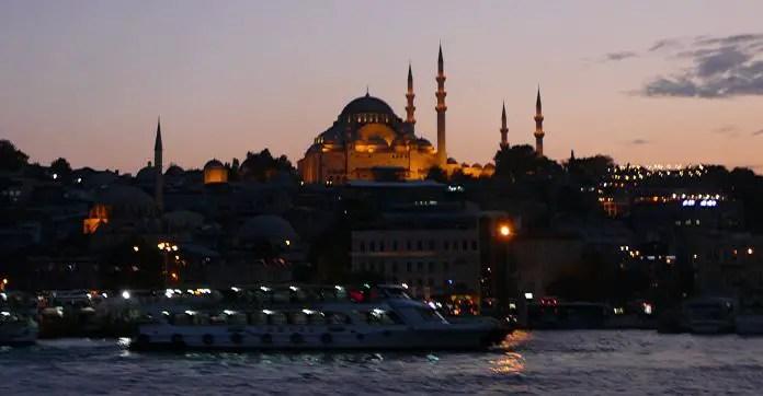 Fähre am Bosporus in Istanbul bei Nacht. Augenommen vom Wasser aus. Im Hintergrund ist die Süleymaniye Moschee zu sehen.