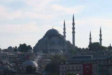 Süleymaniye Moschee im Gegenlicht bei Sonnenuntergang. Ihre vier Minarette sind gut zu sehen und die davor liegenden Gebäude