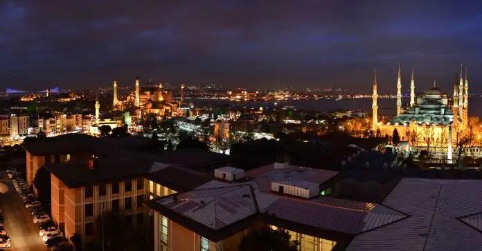 Panoramablick auf Istanbuls Altstadt Sultanahmet in der Nacht. Mit der hell erleuchtete Hagia Sophia und der Blauen Moschee. Im Hintergrund ist die Bosporusbrücke zu sehen und am Himmel ein Flugzeug.