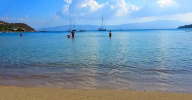 Blick vom Strand auf das Meer vor Bodrum. Menschen und Yachten sind im Wasser zu sehen.