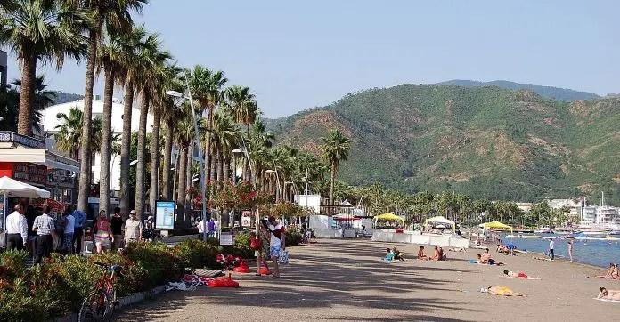 Sandstrand in Marmaris, mit Liegestühlen, Palmen, Meer und Blick auf die Berge im Hintergrund