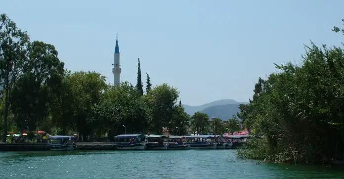 Die Boote am Ufer des Dalyan Fluss im Dorfzentrum und das Minarett der Moschee.