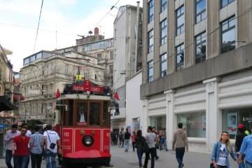 Eine rote Straßenbahn fährt durch die Fußgängerzone Istiklal Caddesi in Istanbul