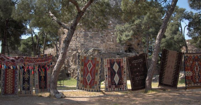 Auf eine Wäscheleine vor der Kadifekale Burg hängen dutzende rot-bunte Smyran Teppiche.