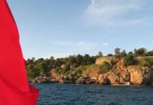 Die rote türkische Flagge mit den Klippen von Antalya in der Türkei.