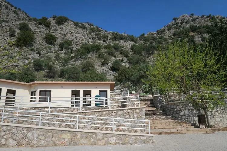 Ein kleines weißes Häuschen mit Toilettanlagen steht am Anfang des Weges auf den Hügel, in dem die Karain Höhle liegt.