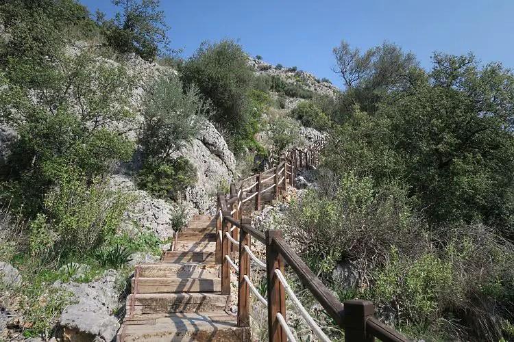 Die Holz- und Steintreppen, die an einem steilen Hügel zur Karain Höhle hinaufführen.