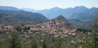 Panoramablick von einem nahen Hügel auf das Bergdorf Ormana mit seinen Steinhäusern und die umliegende Bergkulisse des Taurusgebirges.