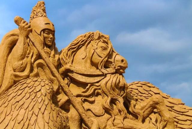 Eine aus Sand geformte Skulptur einer Amazonen Kriegerin mit ihrem Pferd.
