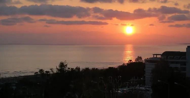Der rötliche Himmel wärend die Sonne noch knapp am Horizont des Strandes von Side zu sehen ist.