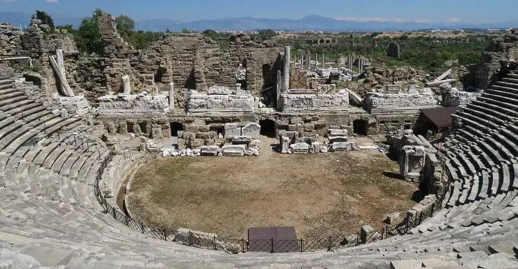 Der Ausblick vom mittleren, obersten Besucherrang des römischen Theaters in Side auf die Ruinen der Bühne und das dahinterliegende Taurusgebirge.