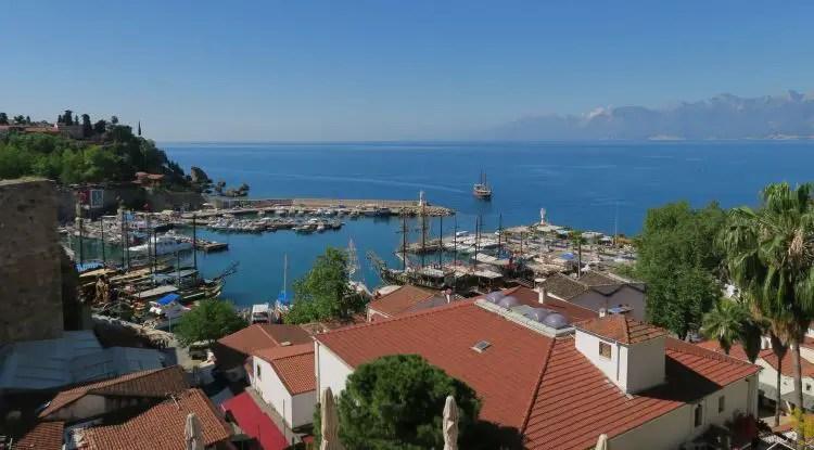 Der Blick von einem Restaurant auf Antalyas Hafenmauern auf den Yachthafen, die Schiffe und Antalyas Altstadt Kaleici.