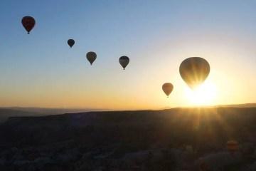 Der Blick aus dem Korb eines Heißluftballon auf die aufgehende Sonne und andere Ballone am Himmel.