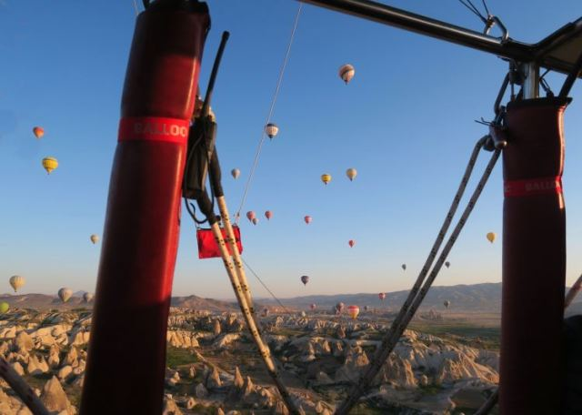 Der Blick aus einem Heißluftballon bei Sonnenaufgang auf Dutzende Ballone am Himmel über Kappadokien.