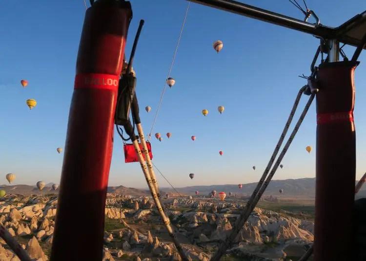 Blick aus dem Korb eines Heißluftballons auf Kappadokien und den Himmel voller anderer Ballone.