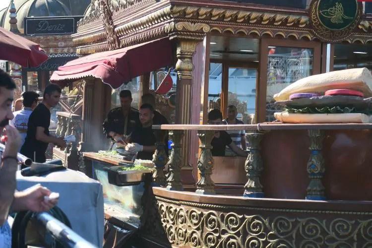 Ein Boot auf dem das typische Street Food Balik Ekmek im Angebot steht. Ein Verkäufer reicht gerade ein Balik Ekmek aus seinem Schiff einem Kunden.