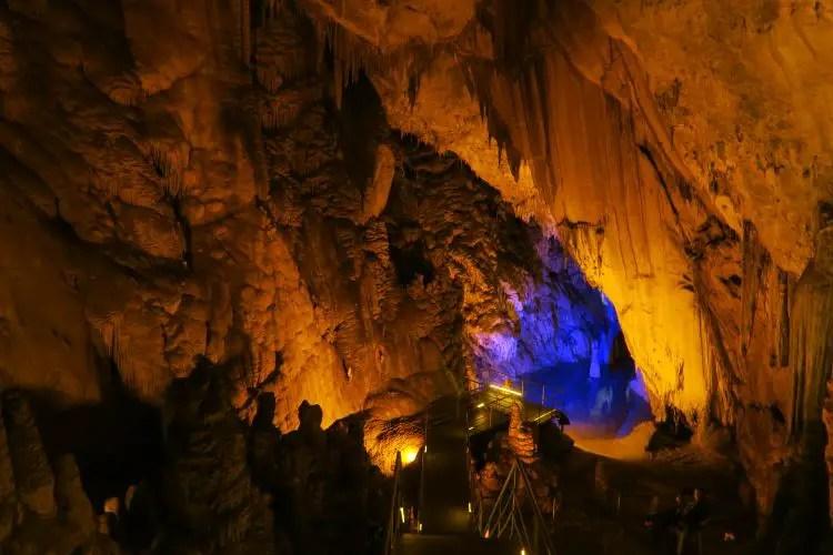 Eine mehrere Meter hohe und breite Höhle mit einem kleinen, blau beleuchteten Höhlensee am Ende.