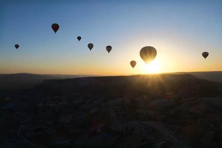 Sonnenaufgang in Kappadokien hinter einem Berg, im Vordergrund ist ein Heißluftballon am Himmel zu sehen.