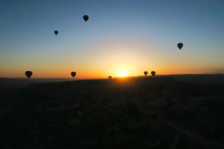 Die Sonne geht mit einem orangenen Licht hinter den Bergen von Kappadokien auf. Davor sind Heißluftballone zu sehen.