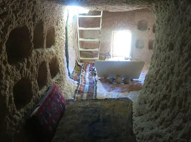 Das zweite Stockwerk mit der Leiter in das nächste und in die Wand gehauene Regale.