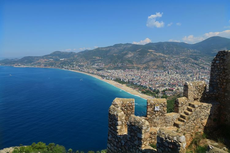 Der Ausblick von den Mauern auf dem Burgberg auf den darunterliegenden Kleopatrastrand, das türkisblaue Meer und die westliche Innenstadt von Alanya.