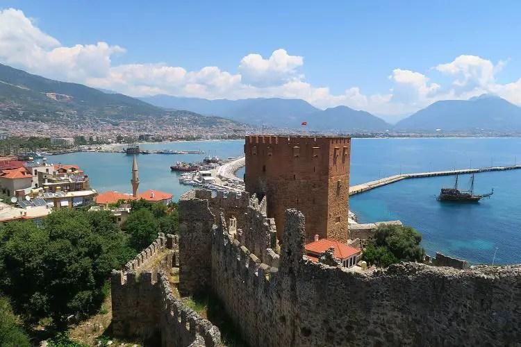Der Blick von den Stadtmauern von Alanya auf den Roten Turm und Hafen der Stadt.