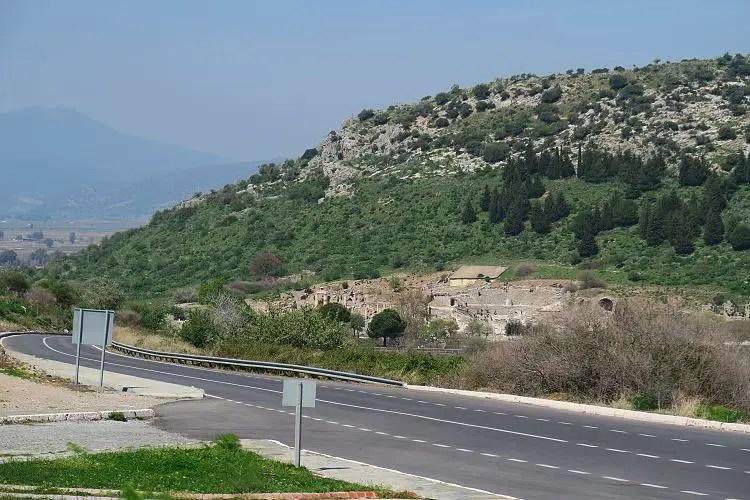 Eine zweispurige Straße mit einem Teil der Ruinen von Ephesos im Hintergrund.