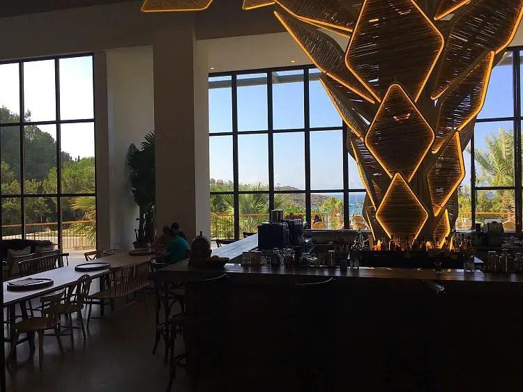 Die große Lobby mit einer Bar und großen Fenstern in Richtung Strand.